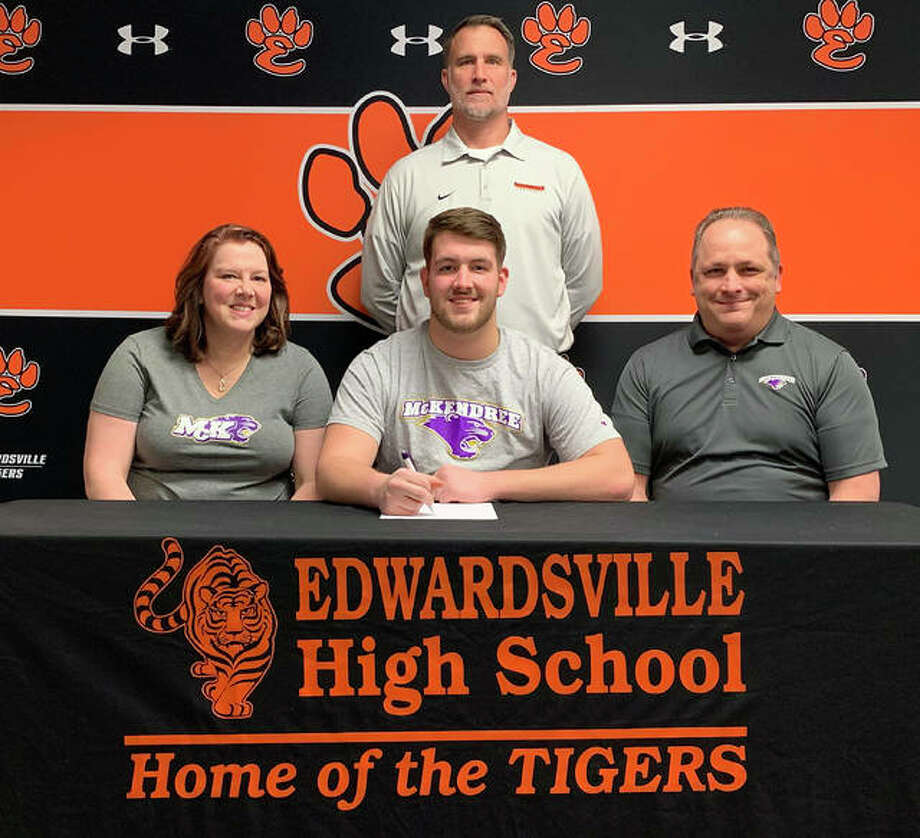 Edwardsville High School senior Cameron Kirkpatrick, seated center, will play college football at McKendree. He is joined in the picture by his family and EHS coach Matt Martin. Photo: Matt Kamp|The Intelligencer
