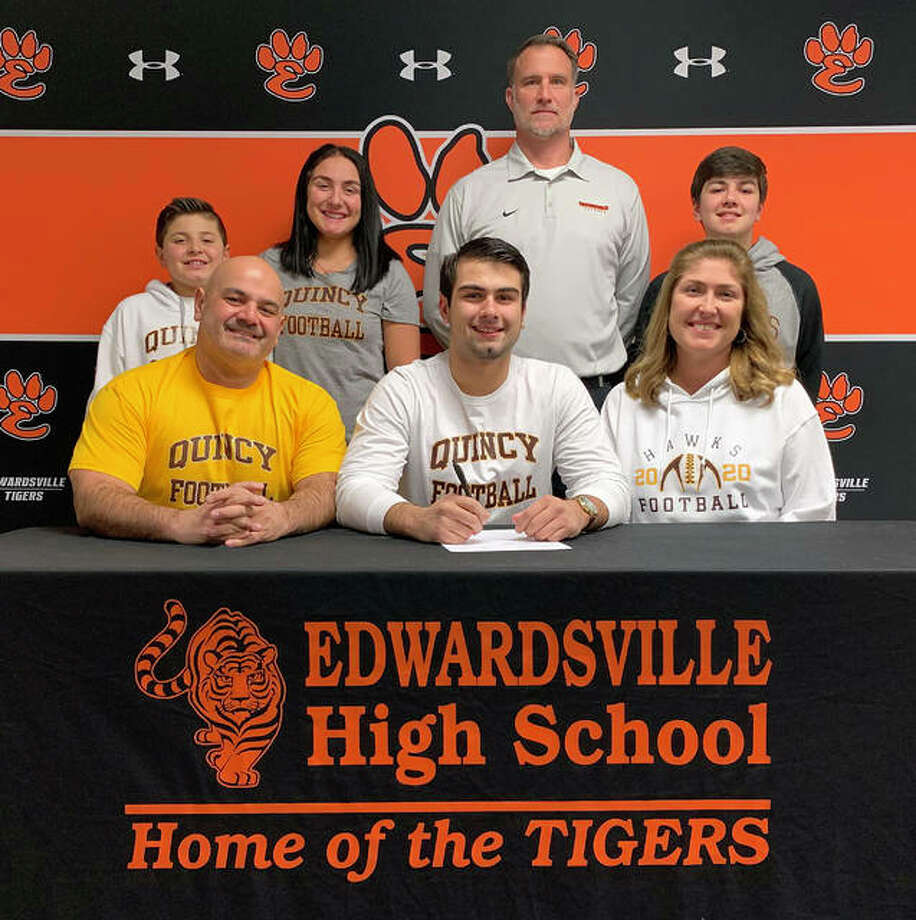 Edwardsville senior Evan Ramirez, seated center, will continue his football career at Quincy. He is joined in the picture by his family and EHS coach Matt Martin. Photo: Matt Kamp|The Intelligencer
