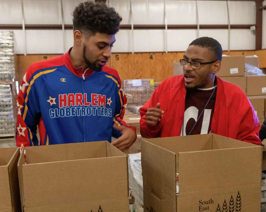 Brayden Coleman, right, of the BISD 18+ group shows Harlem Globetrotter Sweet Lou II what he needs to put into a box of food for seniors. The Friday volunteers at the Southeast Texas Food Bank got some help from the visiting basketball star in assembling food packages for senior citizens on Friday, February 7, 2020. The center boxes up 2500 boxes of food for distribution to seniors every month. Fran Ruchalski/The Enterprise Photo: Fran Ruchalski/The Enterprise / 2019 The Beaumont Enterprise
