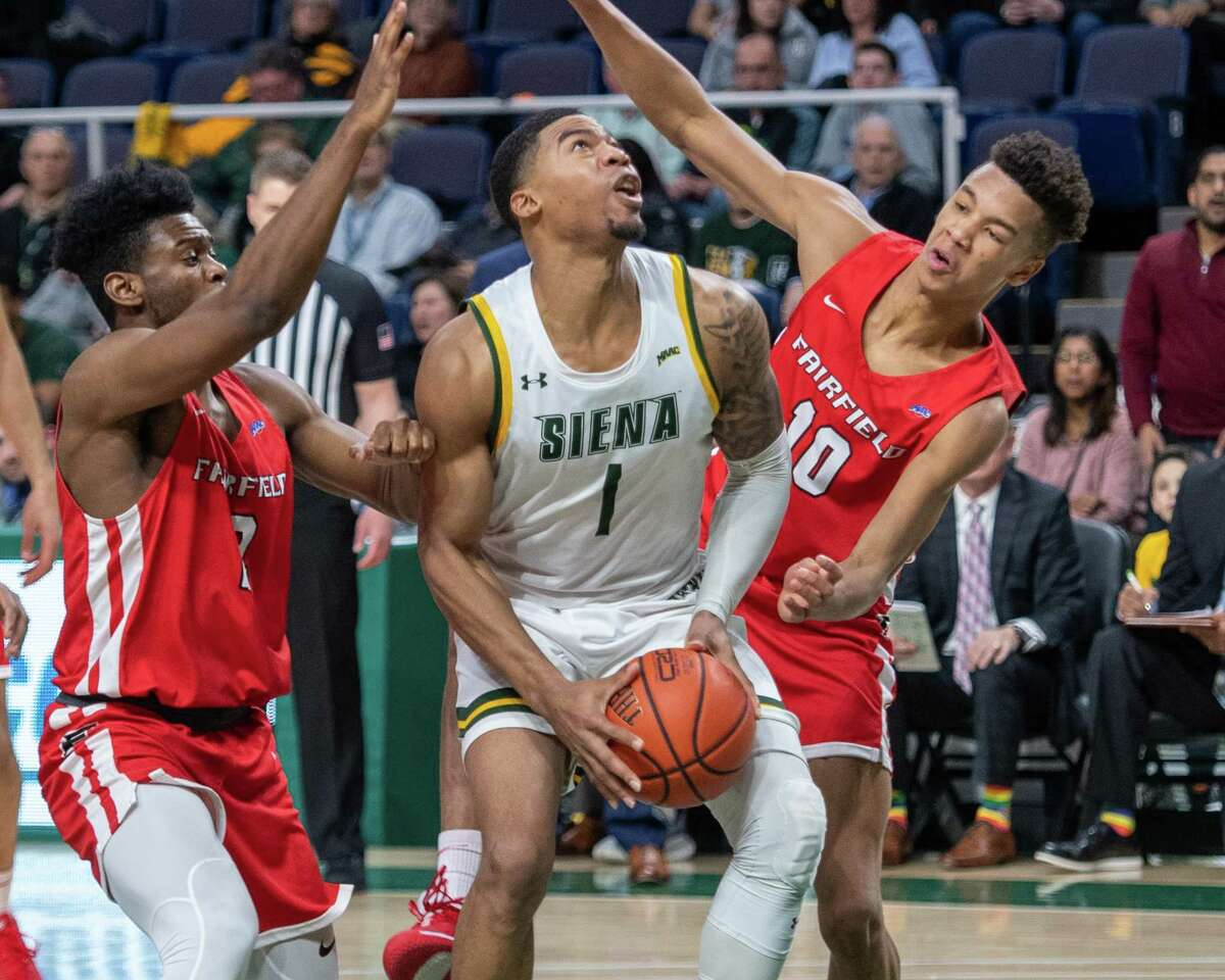 Siena College forward Elijah Burns goes up strong against Fairfield University freshman Allan Jeanne-Rose (10) and jun ior Taj Benning (2) during a Metro Atlantic Athletic Conference game at the Times Union Center in Albany NY on Friday, Feb. 7, 2019 (Jim Franco/Special to the Times Union.)