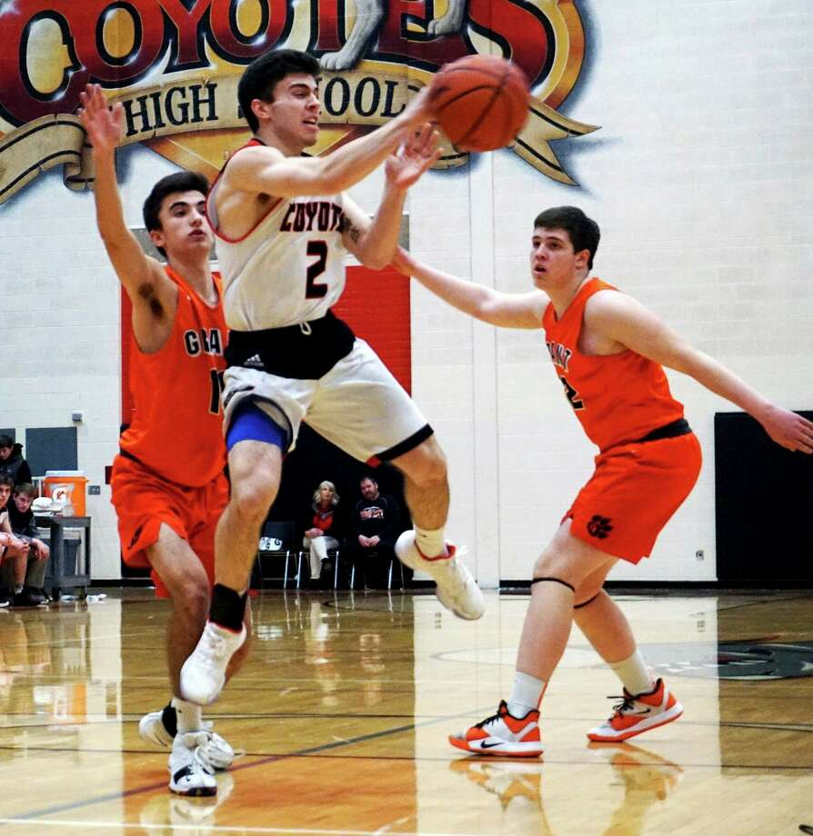 Senior Zac Saez of Reed City passes the ball while airborne during the Coyotes' 63-48 loss to Grant on Friday evening at home. (Pioneer photo/Joe Judd)