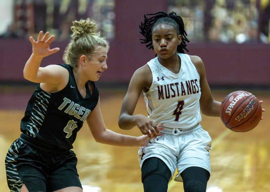 Magnolia West point guard Kamari Portalis (4) dribbles the ball towards the basket while under pressure from A&M consolidated guard Claire Sisco (4) during the second half in a District 19-5A girls basketball game in Magnolia on Wednesday, Feb. 7, 2020. Photo: Gustavo Huerta, Houston Chronicle / Staff Photographer / Houston Chronicle