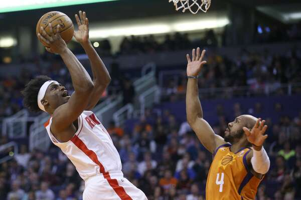 Houston Rockets forward Danuel House Jr., left, shoots over Phoenix Suns guard Jevon Carter (4) during the first half of an NBA basketball game Friday, Feb. 7, 2020, in Phoenix. (AP Photo/Ross D. Franklin)
