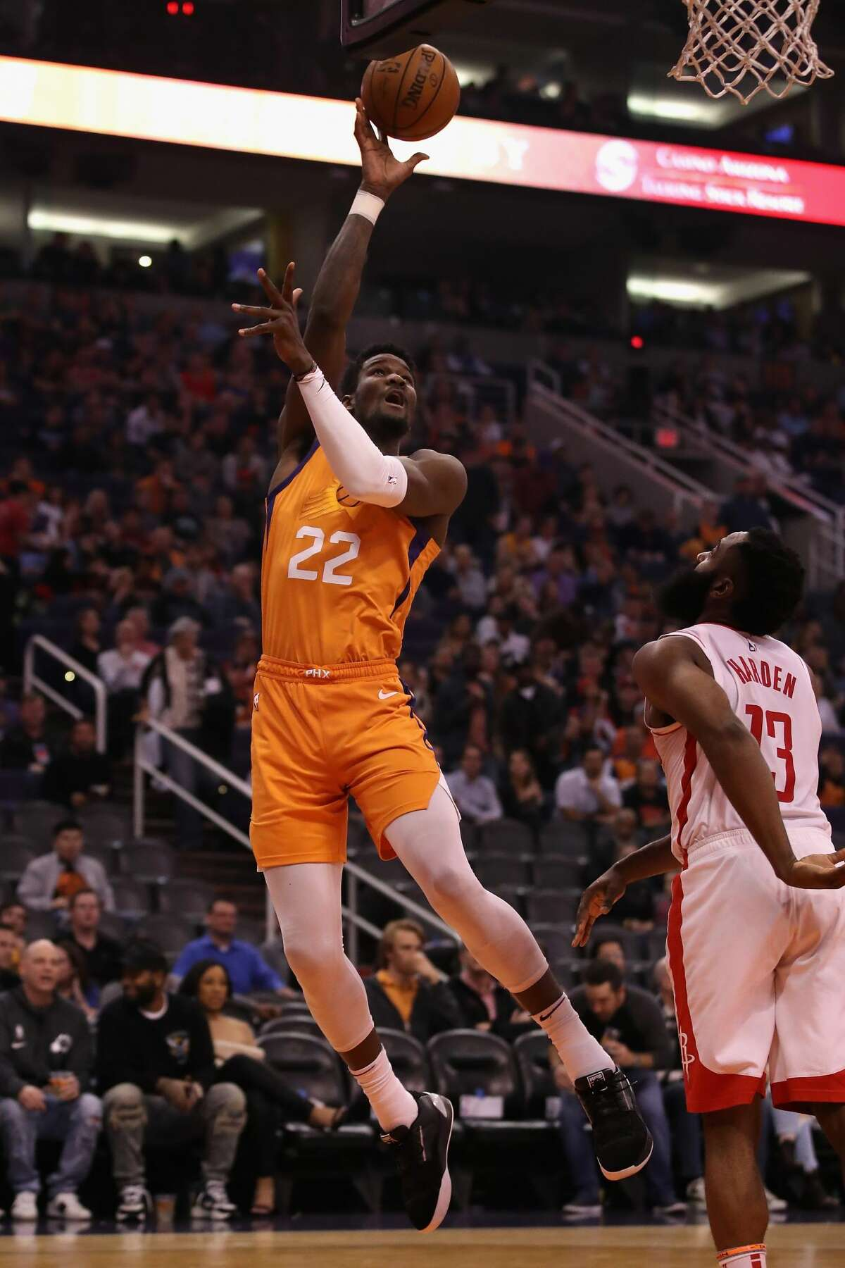 PHOENIX, ARIZONA - FEBRUARY 07: Deandre Ayton #22 of the Phoenix Suns attempts a shot over James Harden #13 of the Houston Rockets during the second half of the NBA game at Talking Stick Resort Arena on February 07, 2020 in Phoenix, Arizona. NOTE TO USER: User expressly acknowledges and agrees that, by downloading and or using this photograph, user is consenting to the terms and conditions of the Getty Images License Agreement. Mandatory Copyright Notice: Copyright 2020 NBAE. (Photo by Christian Petersen/Getty Images)