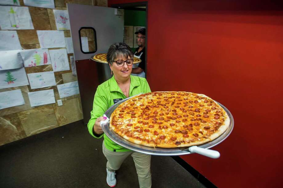 Angela Wojda, center, and Gus Wojda, back, serve 28-inch pizzas during a pizza eating contest hosted by the Midland Daily News and Pizza Sam's Monday at the restaurant. (Katy Kildee/kkildee@mdn.net)
