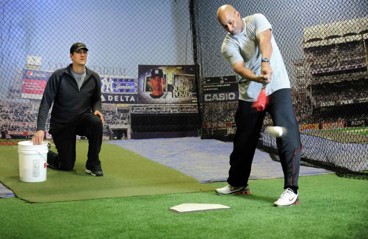 Former Major League Baseball player Mike Porzio, left, tosses balls to former player Angel Echevarria at The Clubhouse, a training facility for young ballplayers at 2245 Black Rock Turnpike in Fairfield, Conn.