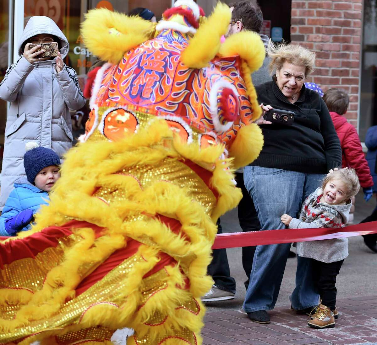New Haven, Connecticut - February 8, 2020: A woman and a child enjoy the sight of a Wan Chi Ming Hung Gar dancing lion during Lunarfest, celebrating the Chinese New Year, the Year of the Rat, and the Chinese culture is highlighted by New Haven's 9th Annual Lion and Dragon Dance Parade that winds down Church Street towards Whitney Avenue to the the Hong Kong Market and Great Wall Restaurant. The dancing Lions are performed by the Wan Chi Ming Hung Gar Institute's lions of New York City, and are a symbol of good luck to people and area merchants. The dragons are handcrafted by area schools and the public.
