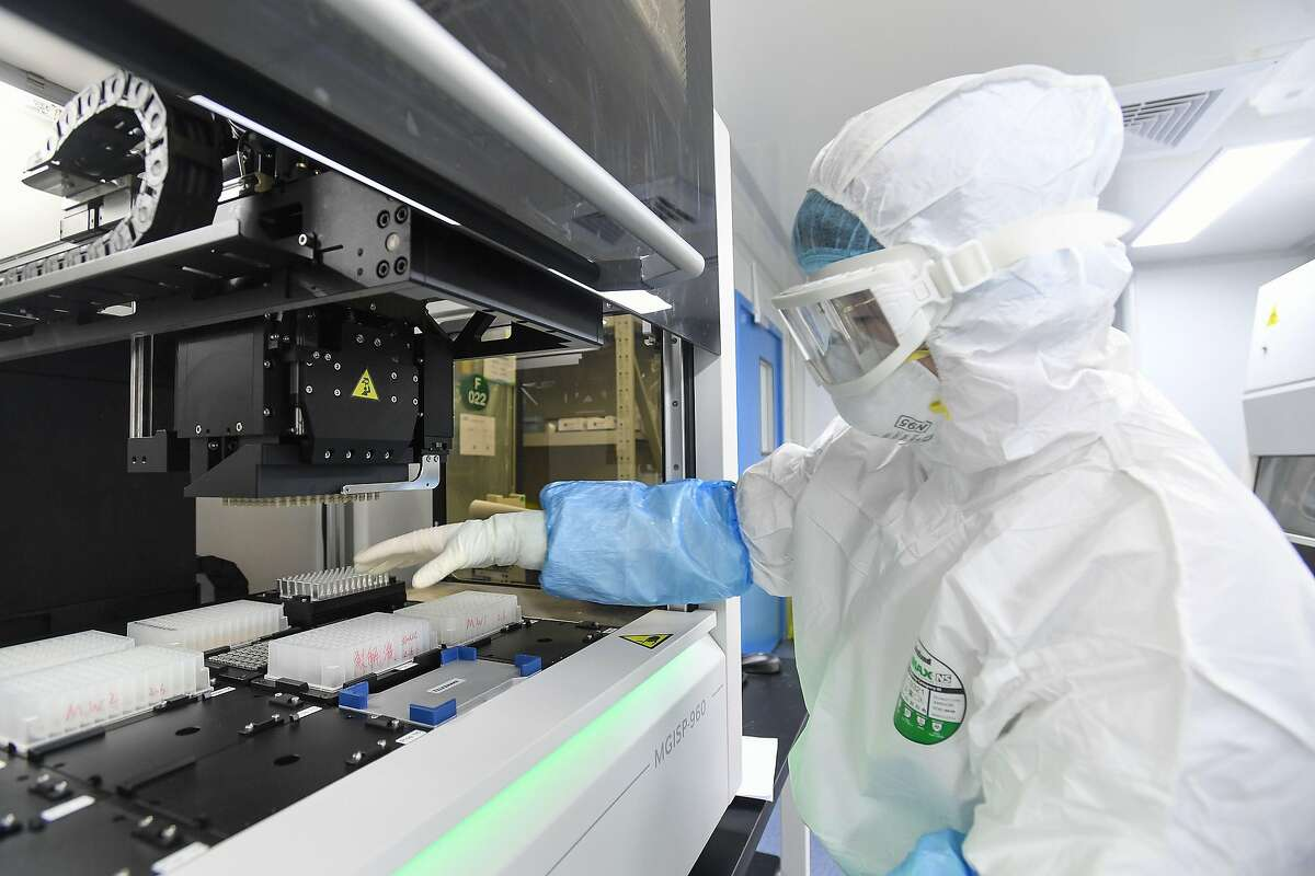 This photo taken on February 6, 2020 shows a laboratory technician working on samples from people to be tested for the new coronavirus at