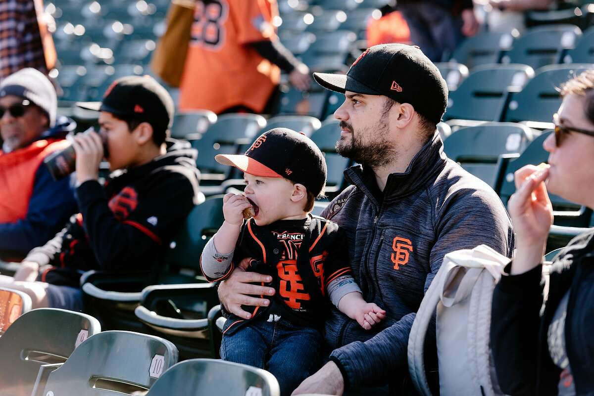 Sean Mosly of Nevada City holds his son Riley Mosly as they sit in the stands during the San Francisco Giants Fan Fest event at Oracle Park in San Francisco, California, U.S., on Saturday, Feb. 8, 2020.