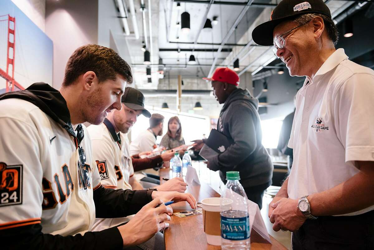 The Giant's Kevin Gausman signs a baseball card for Kevin Fong during the San Francisco Giants Fan Fest event at Oracle Park in San Francisco, California, U.S., on Saturday, Feb. 8, 2020.