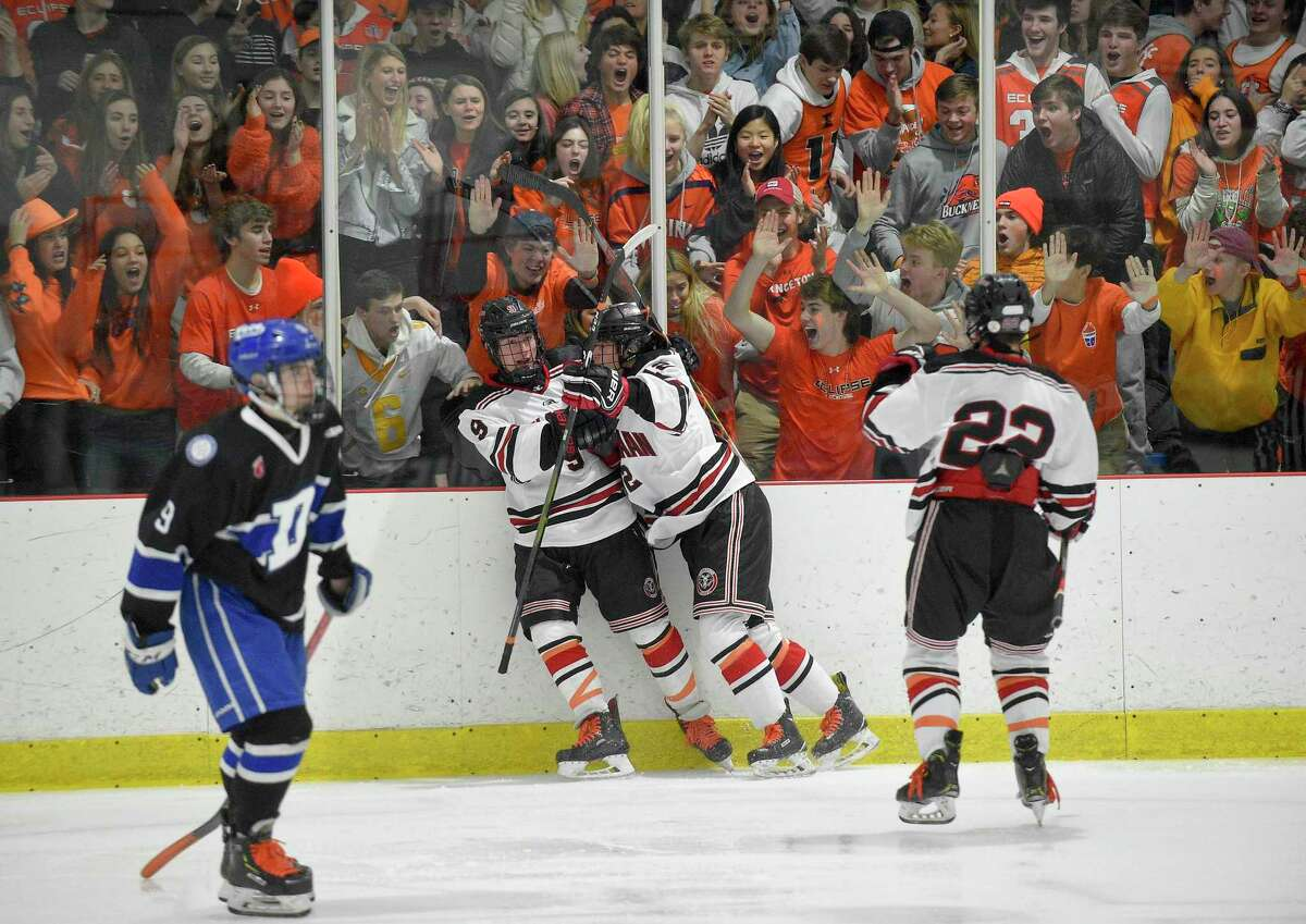 Kaleigh's Krew (dressed in orange) help New Canaan's Jack Johnson (9) celebrate a second period goal against Darien in an FCIAC boys hockey game at the Darien Ice House on Feb. 8, 2020 in Darien, Connecticut. As show of unison, both teams wore orange laces to honor New Canaan student Kaleigh Griffiths, who lost her battle with leukemia. The New Canaan Rams dedicated the game in honor of Kaleigh.
