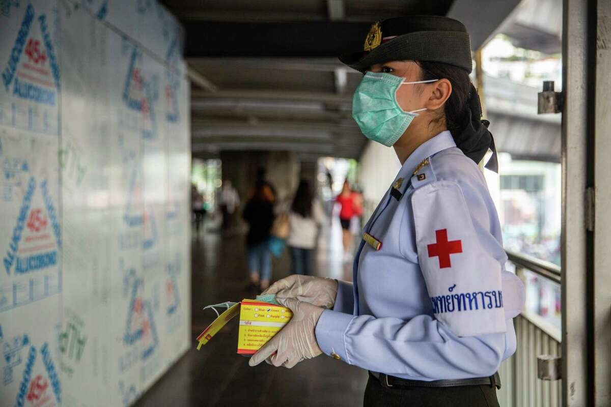 File photo of officials in Thai handing out face masks on Feb. 8, 2020.