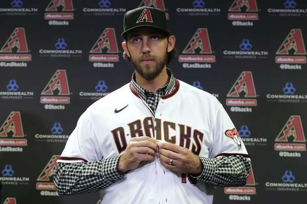 FILE - In this Dec. 17, 2019, file photo, newly acquired Arizona Diamondbacks pitcher Madison Bumgarner puts on a jersey after being introduced during a team availability in Phoenix. The Diamondbacks added a handful of veteran free agents during the offseason, including Bumgarner, outfielder Kole Calhoun, catcher Stephen Vogt and reliever H�ctor Rond�n. The left-handed Bumgarner - a four-time All-Star and 2014 World Series MVP - was the marquee signing, joining the rotation on an $85 million, five-year deal. (AP Photo/Matt York, File)