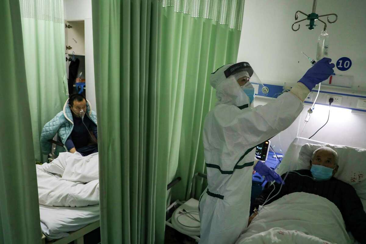 In this Thursday, Feb. 6, 2020, photo, a nurse checks on a patient in the isolation ward for COVID-19 patients at a hospital in Wuhan in central China's Hubei province.