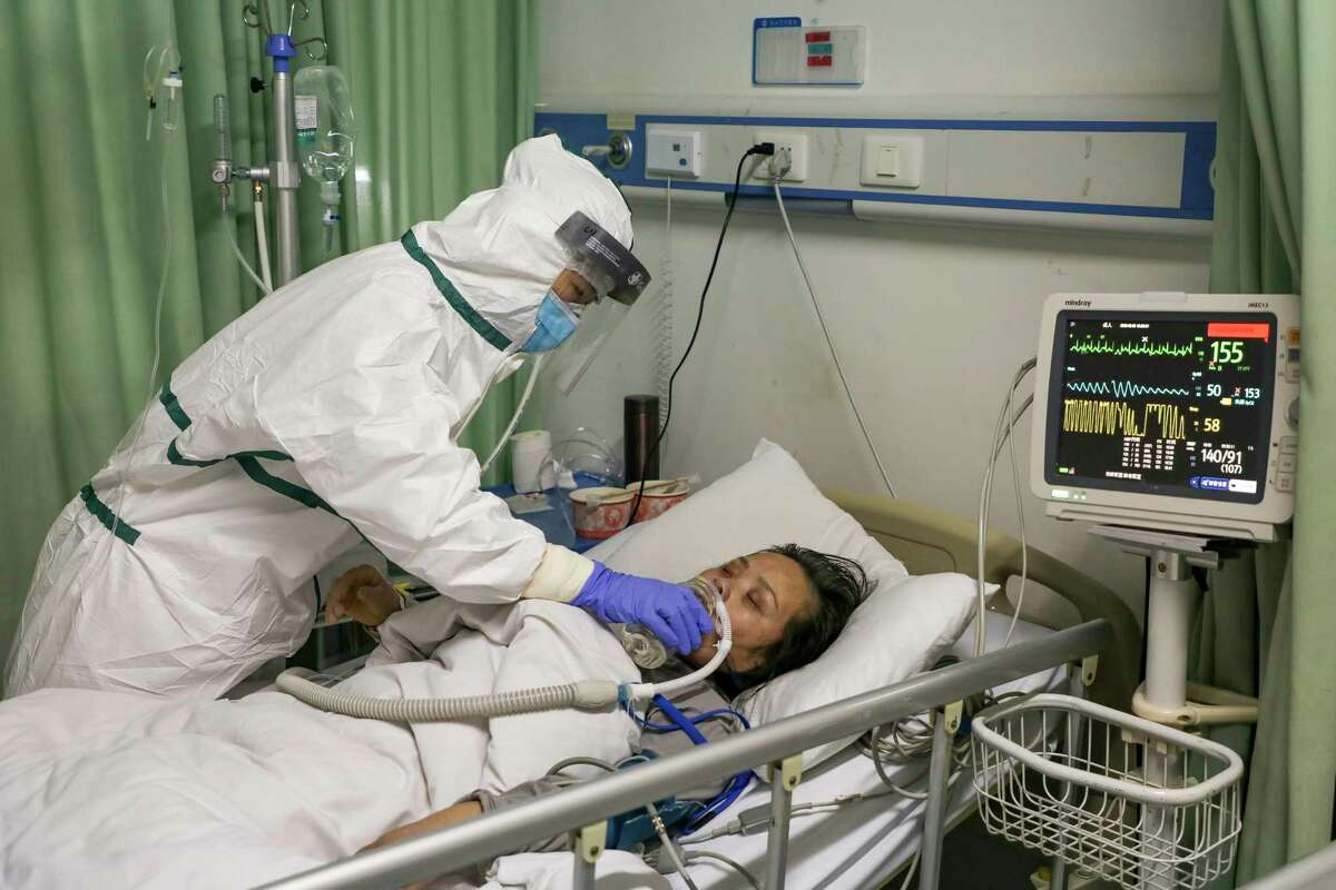 In this Thursday, Feb. 6, 2020, photo, a nurse feeds water to a patient in the isolation ward for COVID-19 patients at a hospital in Wuhan in central China's Hubei province.