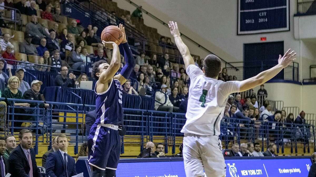 Yale's Azar Swain with a three point shot over Dartmouth's Trevon Ary-Turner