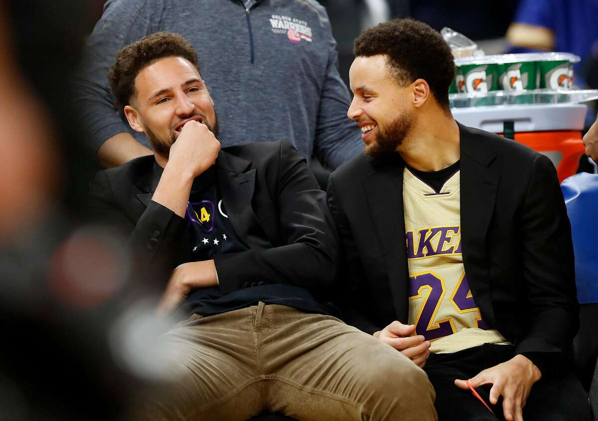 Golden State Warriors' Klay Thompson and Stephen Curry on bench during NBA game against Los Angeles Lakers at Chase Center in San Francisco, Calif., on Saturday, February 8, 2020.