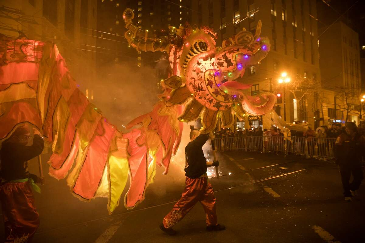 FILE - The Golden Dragon, which takes over one hundred people to hold up runs through some exploding fireworks during the Chinese New Year Parade in San Francisco, Calif. on February 8, 2020. The 2021 event has been cancelled due to concerns of large gatherings contributing to the spread of the coronavirus.