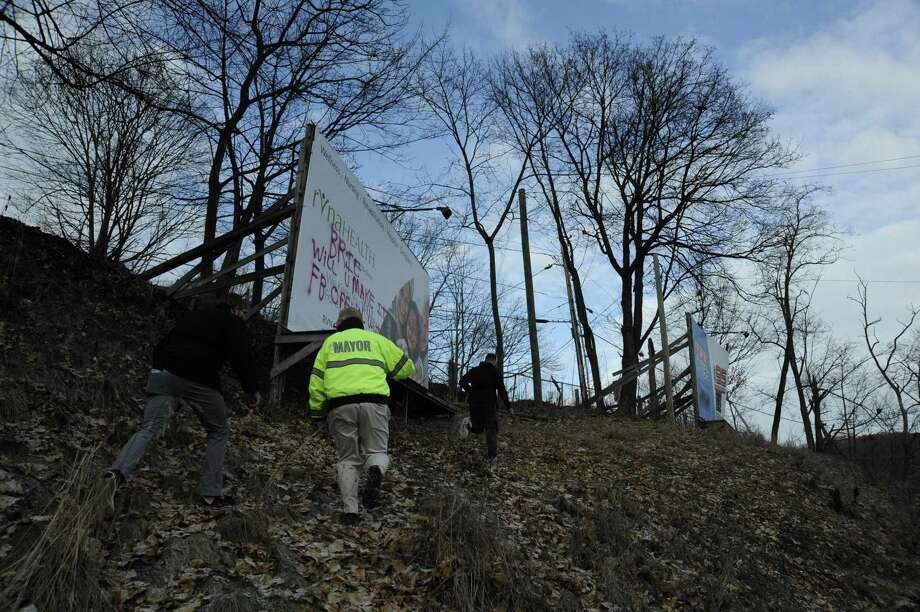 """Danbury Mayor Mark Boughton hikes up a hill overlooking the Padanaram Road section of North Street in Danbury with Lou Milano and Joe Echevarria of WRKI radio Sunday, Feb. 9 2020. Milano spray painted """"love"""" on the billboard, after the city covered up a graffiti reference to the Ku Klux Klan there the night before. Photo: Peter Yankowski /Hearst Connecticut Media"""