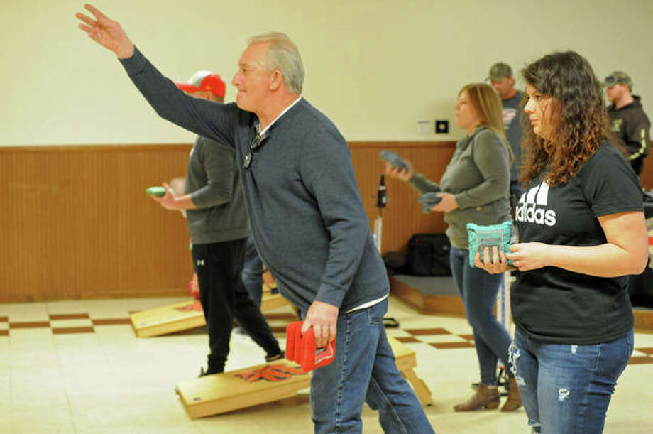 Cornhole tournament contestants from the bi-state area throw during Saturday's competition at the Owl's Club in Alton. The game is similar to horseshoes, using bags instead and slanted wooden platforms with a hole.