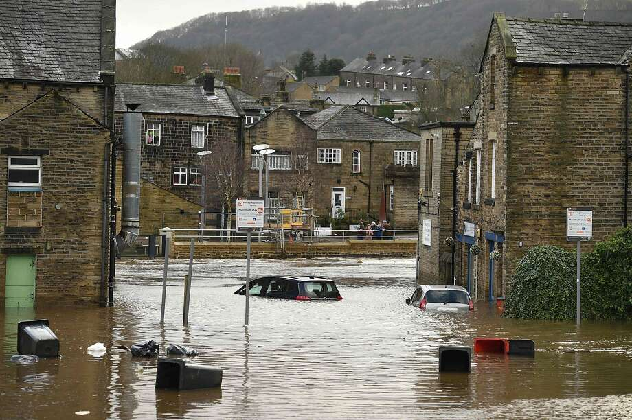 Cars are seen submerged as flood water covers the roads and car parks in Mytholmroyd, northern England, on February 9, 2020, after the River Calder burst its banks as Storm Ciara swept over the country. - Britain and Ireland hunkered down Sunday for a powerful storm expected to disrupt air, rail and sea links, cancel sports events, cut electrical power and damage property. With howling winds and driving rain, forecasters said Ciara would also hit France, Belgium, the Netherlands, Switzerland and Germany. (Photo by Oli SCARFF / AFP) (Photo by OLI SCARFF/AFP via Getty Images) Photo: OLI SCARFF / AFP Via Getty Images