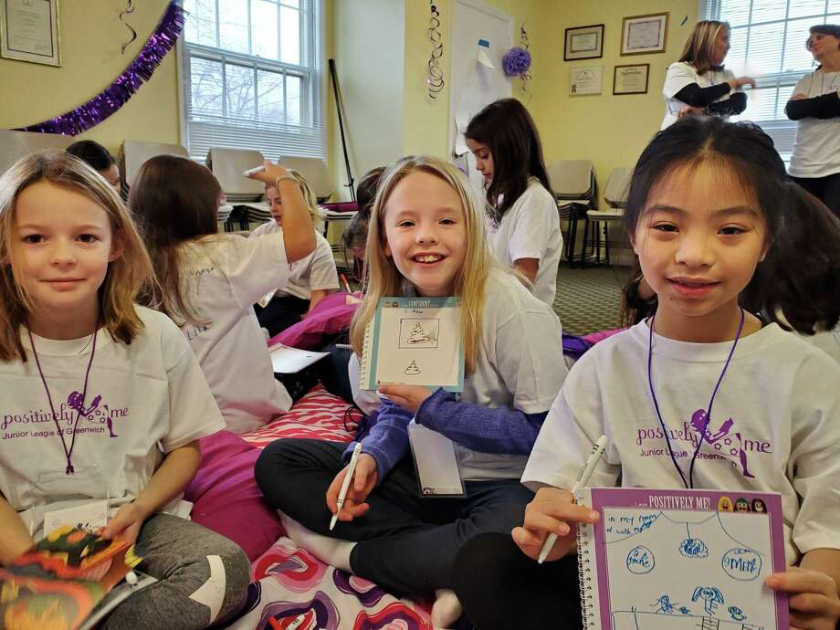 Last weekend's Positively Me event was designed to give 8- and 9-year-old girls the skills to be confident, make good decisions, be assertive, express themselves and cope with peer pressure and bullying. From left, Evie Kelly, Rose McLean and Molly Moy demonstrate their work in their Positively Me self-ref;ection notebooks about how they deal with their emotions. Photo: Contributed / Junior League Of Greenwich /