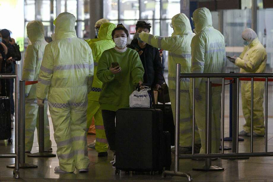 Medical workers wearing protective clothing monitor passengers at the Shanghai South railway station. The death toll in the virus outbreak is 910. Photo: Noel Celis / AFP / Getty Images