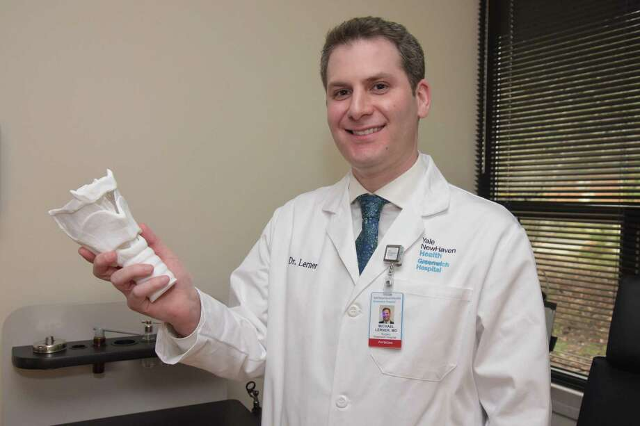 Dr. Michael Lerner, a fellowship-trained Yale Medicine laryngologist, holds a model of the larynx or voice box at the new Yale Voice Center at Greenwich Hospital at 55 Holly Hill Lane, Greenwich. Dr. Lerner is an ear, nose and throat physician specially trained to treat conditions of the larynx Photo: Contributed /