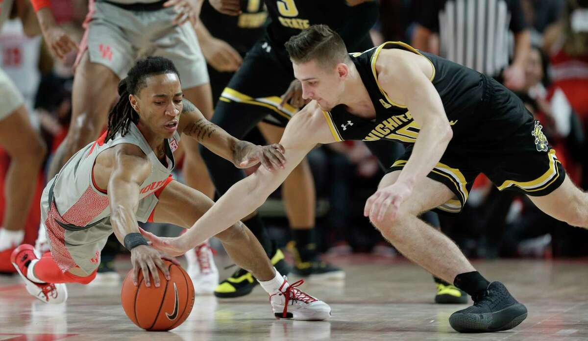Houston guard Caleb Mills, left, and Wichita State guard Erik Stevenson dive for a loose ball during the first half of an NCAA college basketball game, Sunday, Feb. 9, 2020, in Houston.