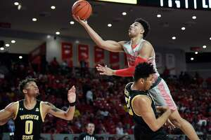 Houston guard Quentin Grimes, top right, shoots over Wichita State center Jaime Echenique during the first half of an NCAA college basketball game, Sunday, Feb. 9, 2020, in Houston.