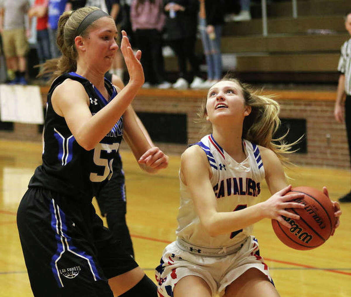 Carlinville's Jill Stayton (right) takes the ball to the basket against Greenville's 6-foot-4 Megan Hallemann during the Cavaliers' SCC victory Thursday night in Carlinville. While the Cavs are back home this week for a Class 2A regional, the Comets open postseason play in Carlyle.