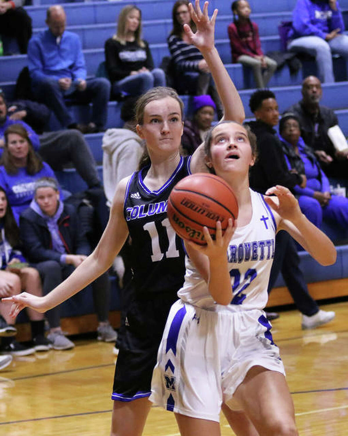 Marquette Catholic's Jillian Nelson scores on a reverse layup after getting past Columbia's Avrie Barthel (11) in a Dec. 23 game in Columbia. Marquette is 23-6 and goes to the Gillespie Class 2A Regional.