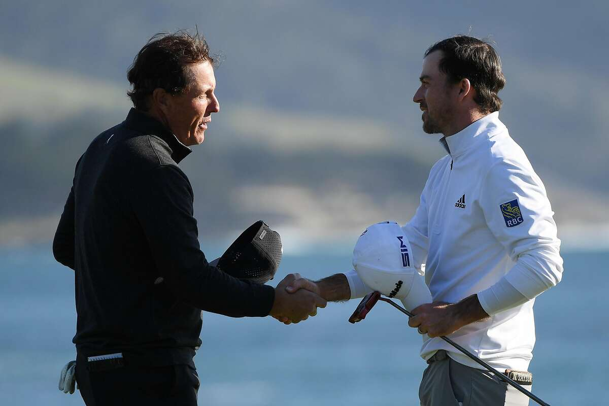 PEBBLE BEACH, CALIFORNIA - FEBRUARY 09: Nick Taylor of Canada shakes hands with Phil Mickelson of the United States on the 18th green after winning the AT&T Pebble Beach Pro-Am at Pebble Beach Golf Links on February 09, 2020 in Pebble Beach, California. (Photo by Harry How/Getty Images)