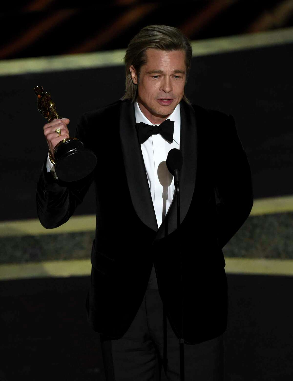 """Brad Pitt accepts the award for best performance by an actor in a supporting role for """"Once Upon a Time in Hollywood"""" at the Oscars on Sunday, Feb. 9, 2020, at the Dolby Theatre in Los Angeles."""