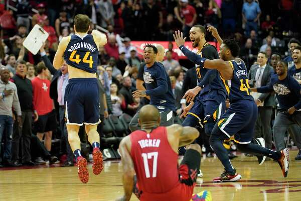 Houston Rockets P.J. Tucker sits on the floor as Utah Jazz Bojan Bogdanovic (44) and teammates celebrates his three pointer to win by one over the Rockets Sunday, Feb. 9, 2020, at Toyota Center in Houston.