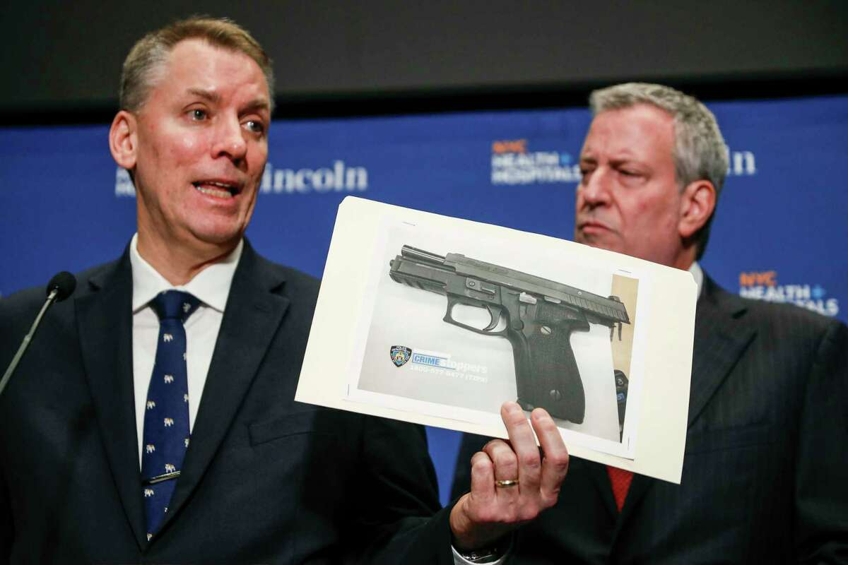 New York City Police Commissioner Dermot Shea, left, holds up an evidence picture of a gun used in an officer involved shooting during a news conference with Mayor Bill de Blasio, Sunday, Feb. 9, 2020, in New York. (AP Photo/John Minchillo)