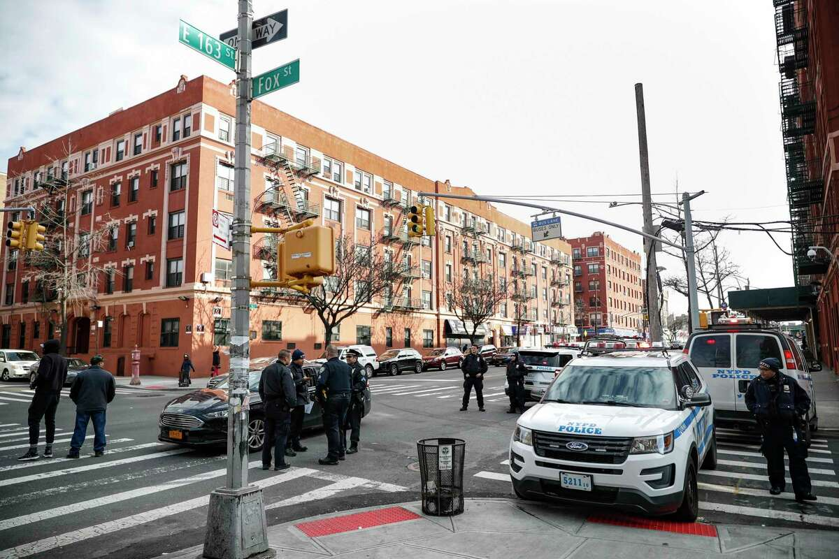 New York City police officers stage work at the scene of a police involved shooting, Sunday, Feb. 9, 2020, in the Bronx borough of New York. (AP Photo/John Minchillo)
