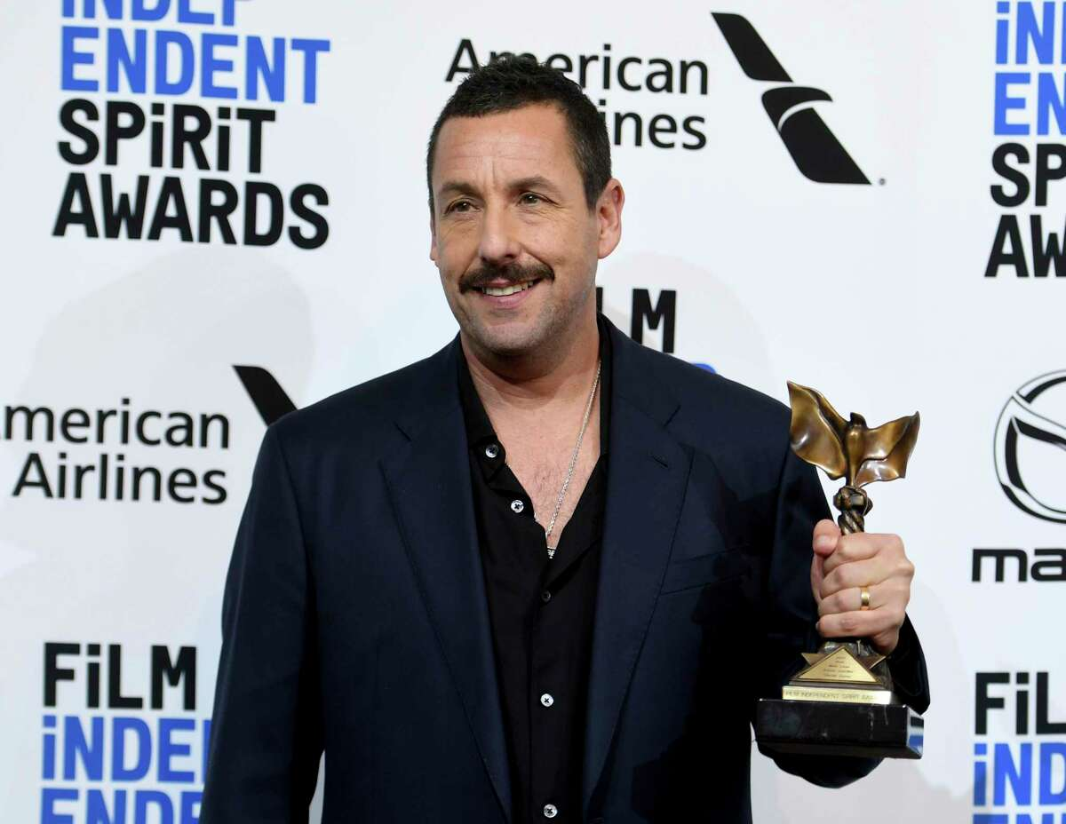 Adam Sandler poses in the press room with the award for best male lead for