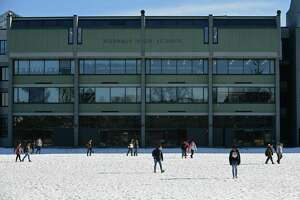 Students leave Norwalk High School on a recent afternoon. The city is considering a plan to build a new Norwalk High School, and if approved, the state would reimburse 80 percent of the construction costs.
