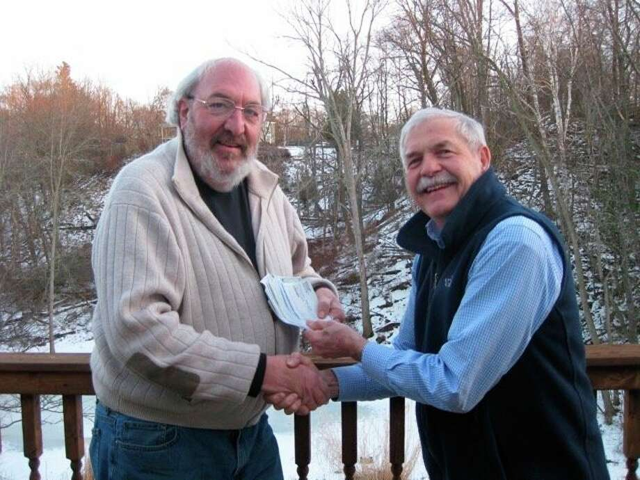 Shown from left: Al Frye of Men Who Care, gives checks to Bob Thomas, a representative from both the Marilla Township Food Bank and Men Who Care. (Courtesy photo)