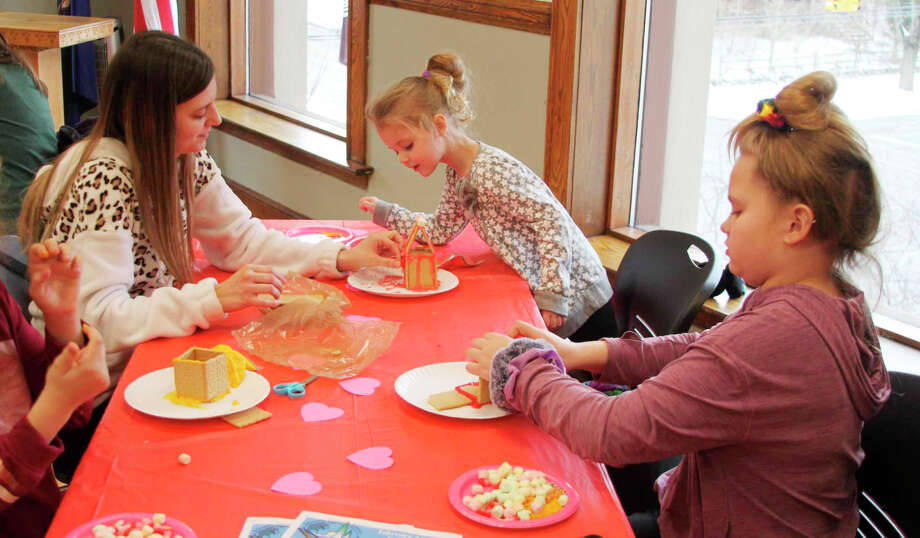 The Love Shack Gingerbread House Building project at the Manistee County Libary on Saturday drew in quite a few children with their parents. They had fun creating Love Shacks commemorating Valentine's Day, which is on Friday. Photo: Ken Grabowski/News Advocate