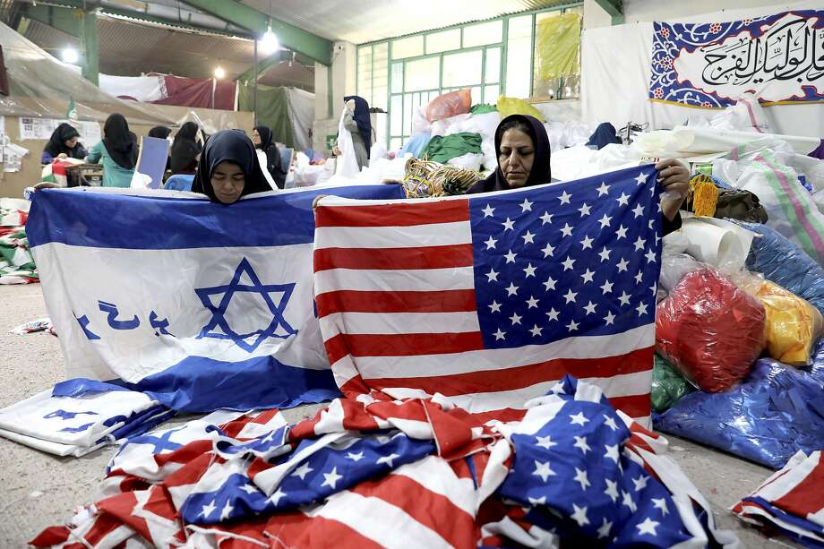 Factory workers fold U.S. and Israeli flags at the Diba Parcham Khomein plant in Heshmatieh in central Iran. The banners are destined to go up in flames at protest demonstrations. Photo: Ebrahim Noroozi / Associated Press