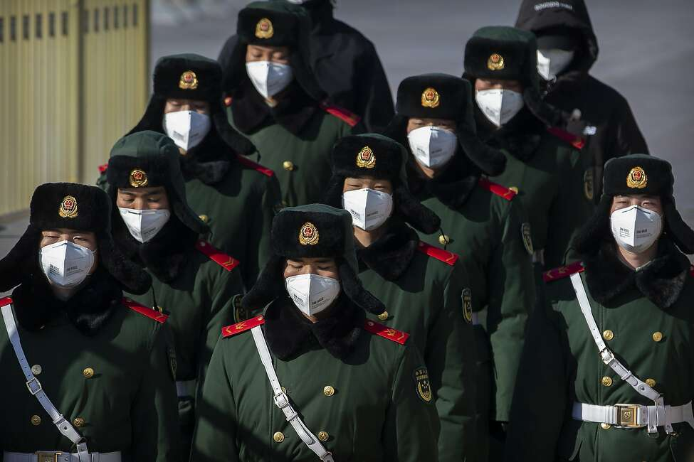 Paramilitary policemen wear face masks as they march in formation into a pedestrian underpass next to Tiananmen Square in Beijing, Tuesday, Feb. 4, 2020. China said Tuesday the number of infections from a new virus surpassed 20,000 as medical workers and patients arrived at a new hospital and President Xi Jinping said