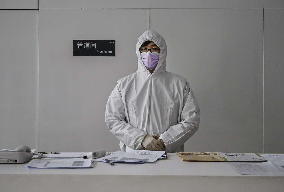 A Chinese worker wears a protective suit as he stands at the lobby desk of an office building while checking people entering on February 10, 2020 in Beijing, China. The number of cases of a deadly new coronavirus rose to more than 40000 in mainland China Monday, days after the World Health Organization (WHO) declared the outbreak a global public health emergency. China continued to lock down the city of Wuhan in an effort to contain the spread of the pneumonia-like disease which medicals experts have confirmed can be passed from human to human. In an unprecedented move, Chinese authorities have put travel restrictions on the city which is the epicentre of the virus and municipalities in other parts of the country affecting tens of millions of people. The number of those who have died from the virus in China climbed to over 900 on Monday, mostly in Hubei province, and cases have been reported in other countries including the United States, Canada, Australia, Japan, South Korea, India, the United Kingdom, Germany, France and several others. The World Health Organization has warned all governments to be on alert and screening has been stepped up at airports around the world. Some countries, including the United States, have put restrictions on Chinese travellers entering and advised their citizens against travel to China.