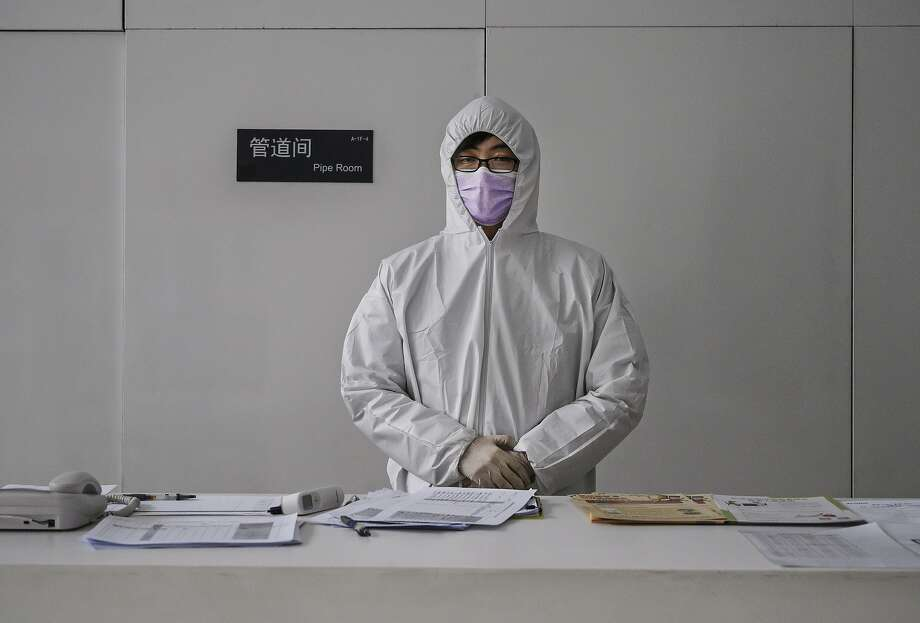 A Chinese worker wears a protective suit as he stands at the lobby desk of an office building while checking people entering on February 10, 2020 in Beijing, China. The number of cases of a deadly new coronavirus rose to more than 40000 in mainland China Monday, days after the World Health Organization (WHO) declared the outbreak a global public health emergency. China continued to lock down the city of Wuhan in an effort to contain the spread of the pneumonia-like disease which medicals experts have confirmed can be passed from human to human. In an unprecedented move, Chinese authorities have put travel restrictions on the city which is the epicentre of the virus and municipalities in other parts of the country affecting tens of millions of people. The number of those who have died from the virus in China climbed to over 900 on Monday, mostly in Hubei province, and cases have been reported in other countries including the United States, Canada, Australia, Japan, South Korea, India, the United Kingdom, Germany, France and several others. The World Health Organization has warned all governments to be on alert and screening has been stepped up at airports around the world. Some countries, including the United States, have put restrictions on Chinese travellers entering and advised their citizens against travel to China. Photo: Kevin Frayer, Getty Images