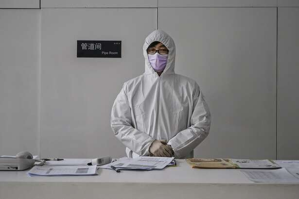BEIJING, CHINA - FEBRUARY 10: A Chinese worker wears a protective suit as he stands at the lobby desk of an office building while checking people entering on February 10, 2020 in Beijing, China. The number of cases of a deadly new coronavirus rose to more than 40000 in mainland China Monday, days after the World Health Organization (WHO) declared the outbreak a global public health emergency. China continued to lock down the city of Wuhan in an effort to contain the spread of the pneumonia-like disease which medicals experts have confirmed can be passed from human to human. In an unprecedented move, Chinese authorities have put travel restrictions on the city which is the epicentre of the virus and municipalities in other parts of the country affecting tens of millions of people. The number of those who have died from the virus in China climbed to over 900 on Monday, mostly in Hubei province, and cases have been reported in other countries including the United States, Canada, Australia, Japan, South Korea, India, the United Kingdom, Germany, France and several others. The World Health Organization has warned all governments to be on alert and screening has been stepped up at airports around the world. Some countries, including the United States, have put restrictions on Chinese travellers entering and advised their citizens against travel to China. (Photo by Kevin Frayer/Getty Images)