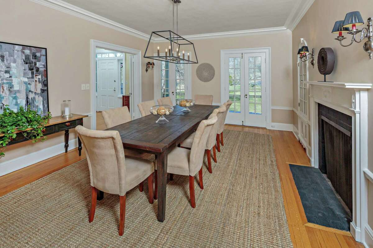 In the formal dining room there is a fireplace, two built-in china cabinets, and French doors to the veranda.