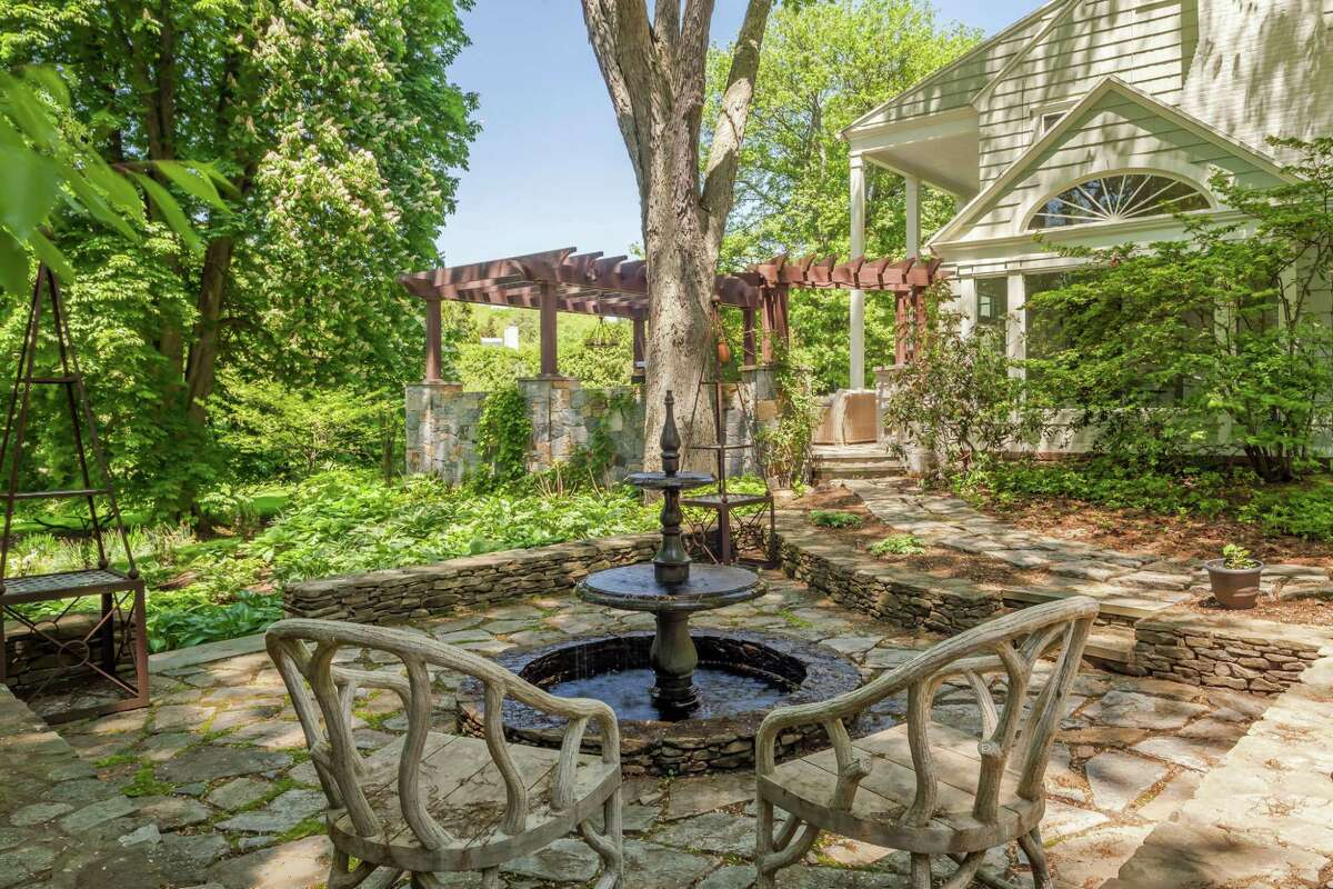 This property has several stone patios and terraces, one with a pergola and one with a fountain.