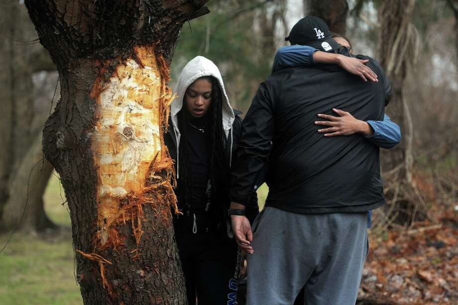 Three people gather next to a tree that was damaged by one of the two vehicles involved in a fatal accident on River Road in Shelton. Photo: Ned Gerard / Hearst Connecticut Media File / Connecticut Post