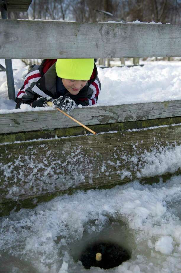 A young angler during a past Winter Free Fishing Weekend waits excitedly to see what will pop up from the icy water. Everyone can fish for free-- no license needed-- during the 2020 Free Fishing Weekend, Feb. 15-16. (Courtesy photo/David Kenyon/Michigan DNR) / 2012 State of Michigan